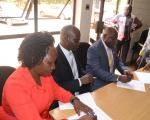 UBTEB Executive Secretary Oyesigye ( R) signing MOU with UGAPRIVI National Chairperson Ndemere (C) in March 2017